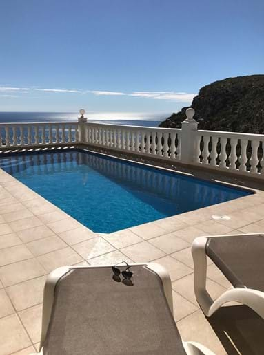 Sun loungers by the pool with a sea view