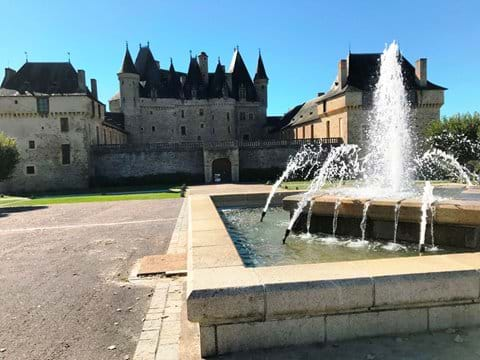 Turreted chateau Jumilhac in the background with a working fountain in the foreground