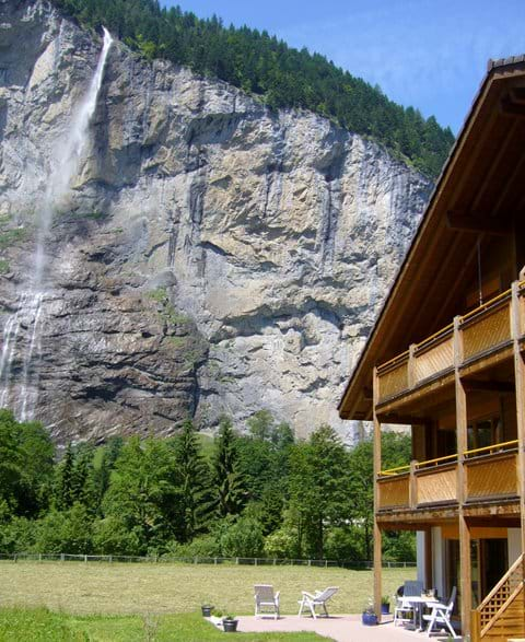 Sunny terrace with mountain and waterfall views.