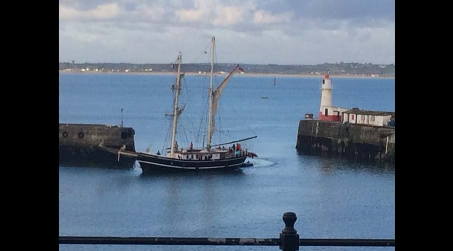 Long boat arriving in Newlyn harbour