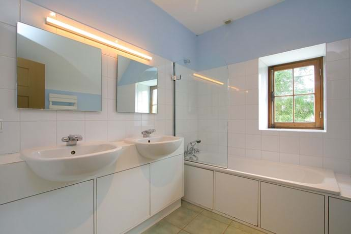 One of the two bathrooms in the Farmhouse with shower over bath, twin sinks and WC