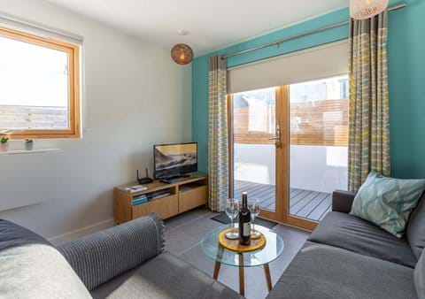 Feet up, curl up and doze off on the large comfy sofa bed looking out onto the south facing decking area or in front of the tv