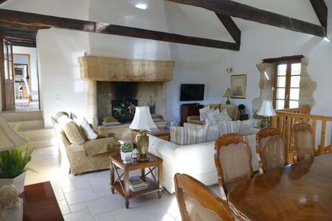 A view of the lovely sitting room in Le Chataignier with exposed beams and large stone fireplace