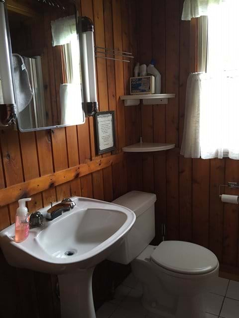 Bathroom has a shower, sink, toilet and old medicine cabinet .
