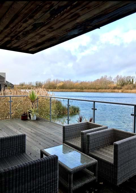 Outdoor seating on spacious decking area overlooking a lake