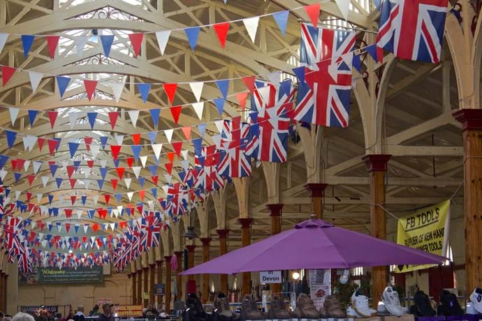 Union Jacks and bunting line the ceiling in the large Barnstaple Panier Market