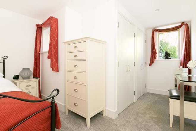 Spacious, carpeted bedroom and dressing area.