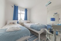 The blue bedroom has twin beds and a small seaglimpse!