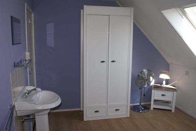 Een van de slaapkamers met wasbak en kledingkast