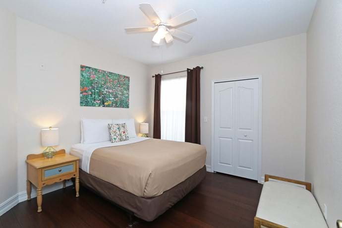 Bedroom 2  at 13-102 with walk in closet, chest of drawers, large TV, ceiling fan and air con