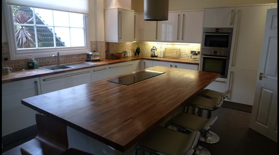 Kitchen featuring double oven, two fridge freezers, compact dishwasher, washing machine, tumble dryer, microwave, electric hob, 4 slice toaster