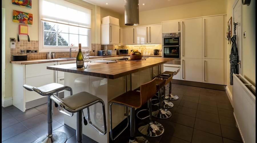 Kitchen with large island, barstools, electric hob, double oven, 2 fridge freezers, washing maching and dryer