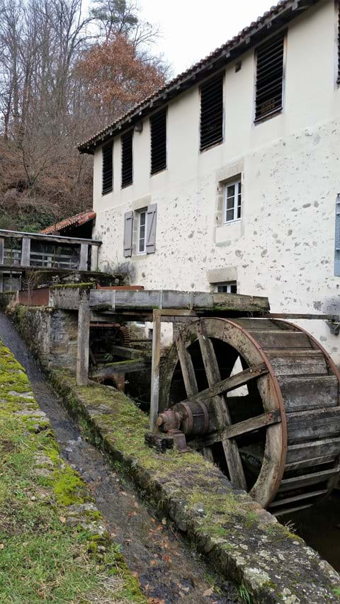 Old white 3 story building on slope with water wheel in wooded area