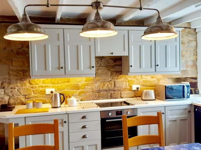 The under-cupboard lighting enhances the original stone walls