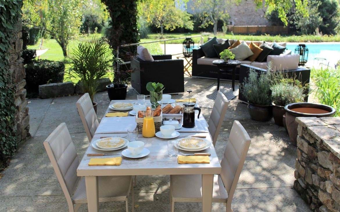 A dressed table with chairs on a shaded patio