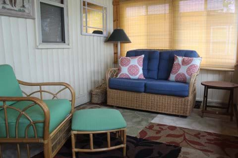 Front porch with wicker gliding love-seat and chair with ottoman.