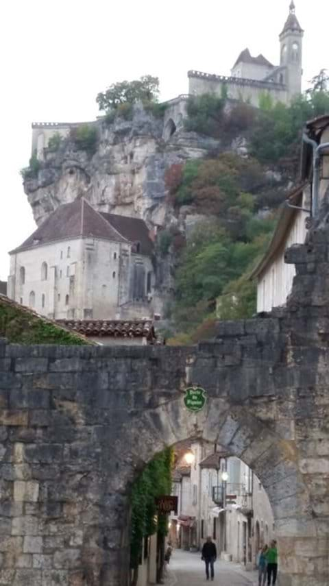Rocamadour a church perched on a hill as seen through a arched bridge with ancient streetst,