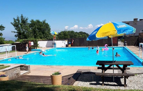 Heated outdoor pool with sun loungers and play area