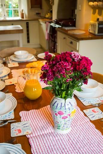 A table with flowers laid for breakfast in an Exmoor holiday cottage kitchen