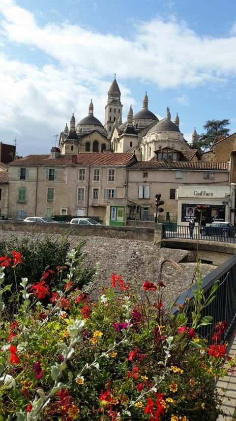 The cathedral in Perigueux taken from a flower lined bridge in Summer