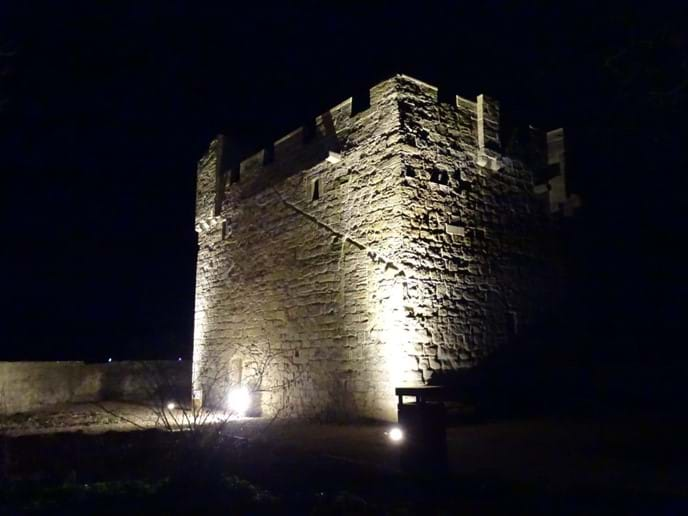 The Pele Tower is illuminated at night, which is very atmospheric