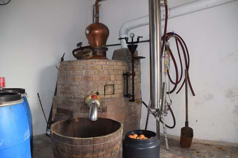 The distillery with apples fermenting in the blue barrel