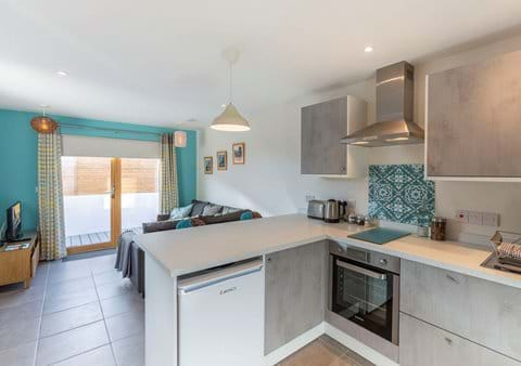 Modern funky living area with fully fitted kitchen, breakfast bar and corner sofa