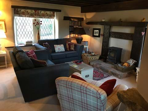 Beamed sitting room with wood burner