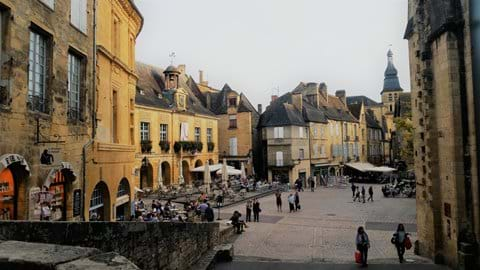 Yellow stone buildings with arches on main square in Sarlat le Caneda