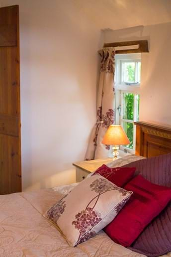 CLose up of a bedroom with bedspread and cushions in a holiday cottage bedroom in Devon