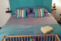 Wooden cot and bedding provided for babies at Chapel Bay Lodge