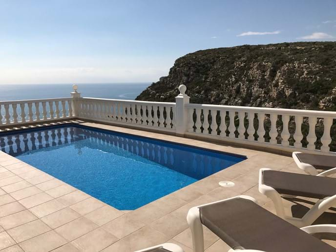 Across the pool terrace with sun loungers, looking out to sea