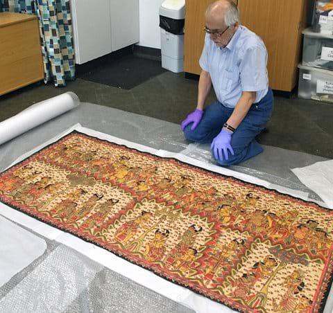 Examining Balinese painting on cloth at Nuneaton Museum