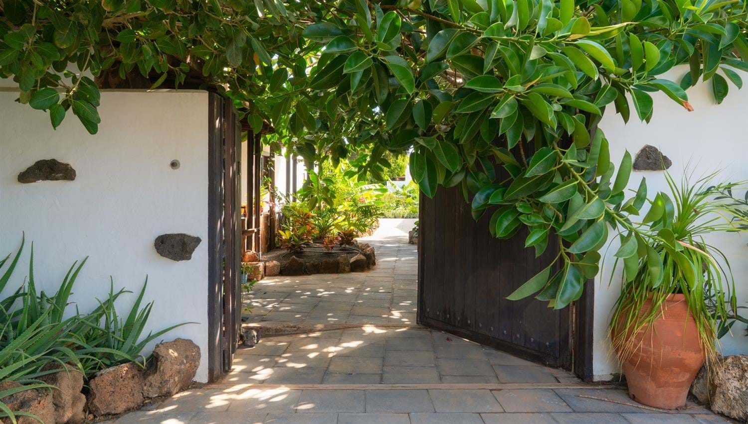 Large old wooden gate opening into The Secret Garden Villa at Finca Botanico in Lanzarote