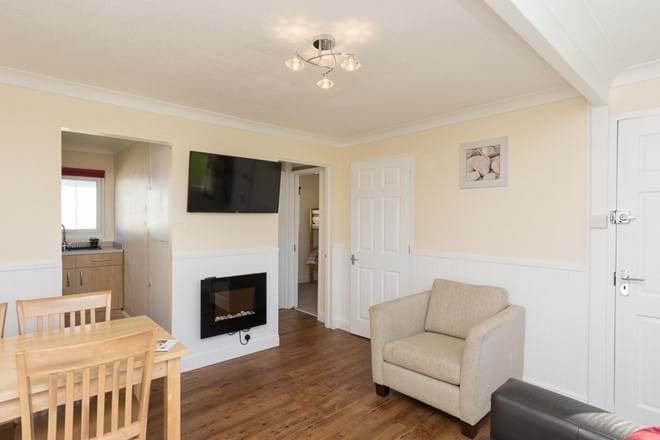 Spacious open plan sitting/dining/kitchen area with feature electric fire & digital TV