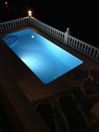 The heated pool at night with underwater lighting
