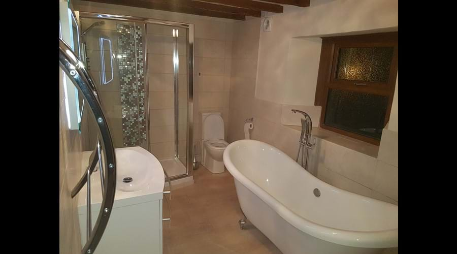 New for 2018 luxury stylish spacious bathroom with curved shower cubicle and power shower, double ended roll top freestanding bath, complemented with floor mounted tap.