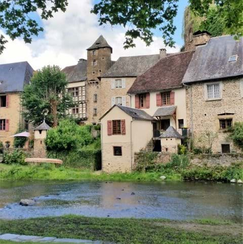 Segur-le-chateau with the river in front of old houses