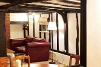 The sense of space in enhanced by the enormous mirror in the living room of this self-catering cottage in Suffolk