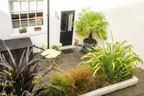 Patio garden lower section with plants, barbecue, bench seat and bistro table and 2 chairs