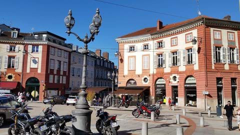 Large square with traffic and surrounded by red bricked buildings and 3 bulb lamp posts in central Limoges