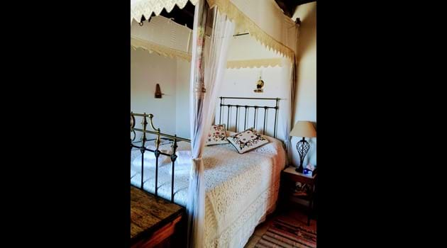 Antique Cypriot four poster bed with handmade lace bedding
