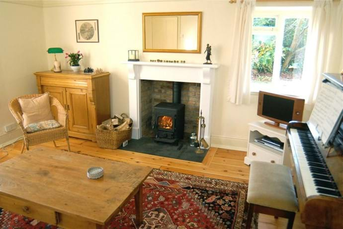 Family room with wood burner, piano, games cupboard. And now with a much bigger TV than the one shown in the picture!