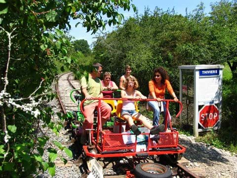 Family of five ride the Velorail on a disused railway line in the Dordogne