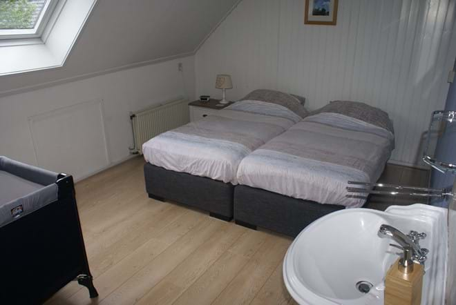 One of the twin bedrooms with basin, wardrobe and boxspring beds (here with cot)
