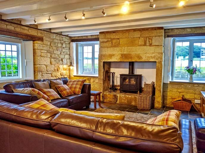 The ground floor is open plan with exposed stone walls and a slate floor. The windows at the front look out across the fields to the medieval Pele Tower opposite - hence the cottage
