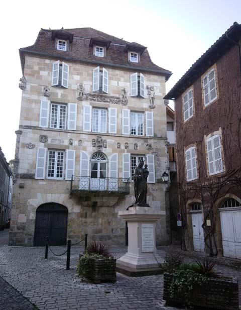 Beaulieu sur Dordogne  old shuttered 5 story house with madonna statue outside on standp