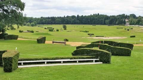 A small white fenced jump on the very green racecourse surrounded by trees in Arnac Pompadour