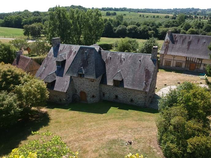 Aerial view of The Farmhouse showing the Barn across the courtyard and large garden