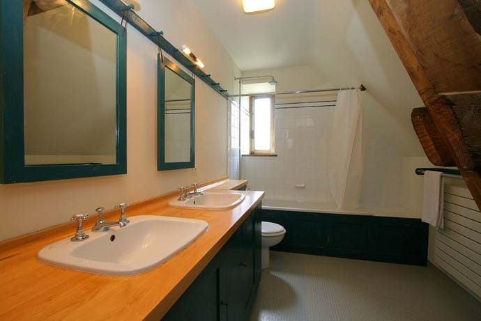 The family bathroom with shower over bath, twin basins and WC.